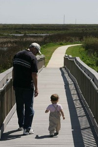 A_man_and_toddler_take_a_leisurely_walk_on_a_boardwalk