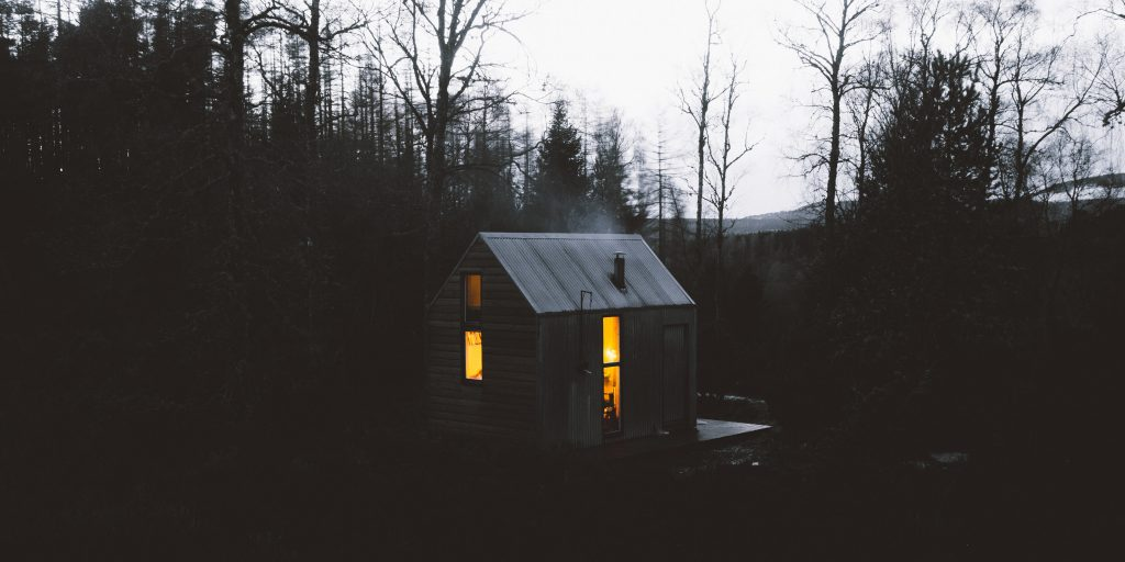 A cabin lit from within at dusk in a remote forest in Scotland.